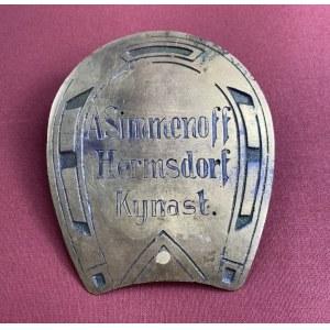 """[Zamek Chojnik,Karkonosze] Tabliczka wizytowa w kształcie podkowy. Napis: """"A.Simmenoff, Hermsdorf, Kynast"""". Mosiądz. Ok.1900-1945 r. Wym 10 x 8,5 cm"""