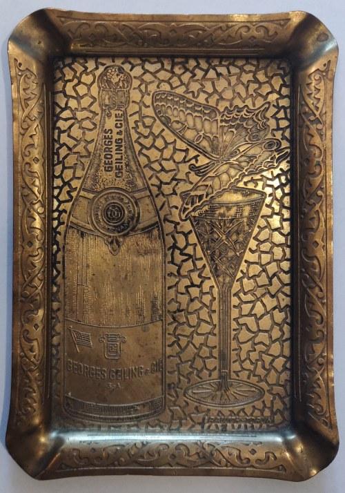 POZNAŃ, TORUŃ. Mosiężna popielniczka z reklamą wytwórni gronowych win musujących: butelka z napisem ...