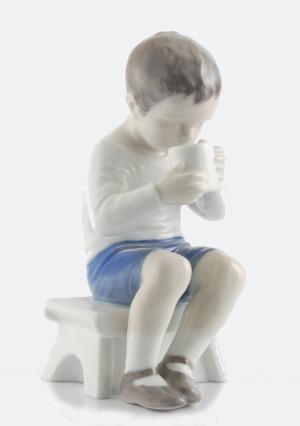 Figurka chłopca pijącego z kubka