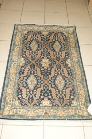 Petit tapis en laine, à décor géométrique sur fond bleu. 120 x 75 cm