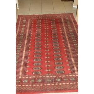 Tapis Boukhara en laine, à décor géométrique sur fond rouge. 170 x 120 cm